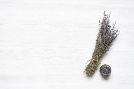 Dried lavender flower branch on a wooden table background with copy space. Herbal medicine concept.