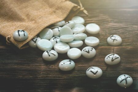 Stone runes on a wooden table background. Futune reading concept.