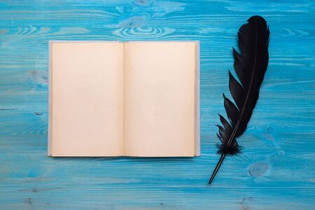 Blank open book with empty pages for copy space and a quill pen on a writer table background.