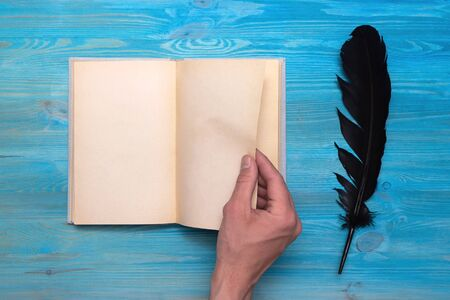 Hand holding blank open book with empty pages for copy space on a writer table background.