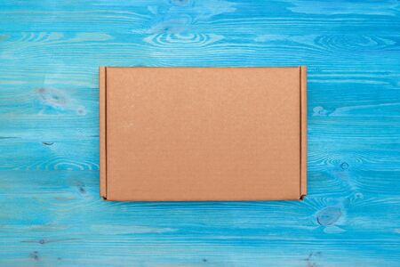 Closed parcel cardboard box on a blue wooden table background. Delivery service concept.
