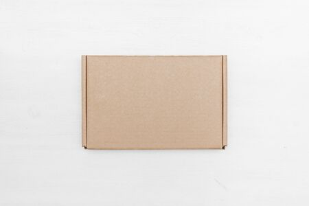 Blank cardboard parcel box on a white table background.