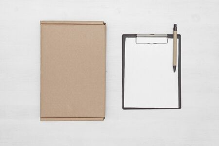 Blank cardboard parcel box and an empty invoice document mock up on a white table background. Banco de Imagens