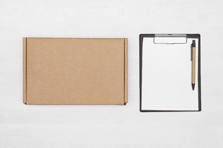 Blank cardboard parcel box and an empty invoice document mock up on a white table background.