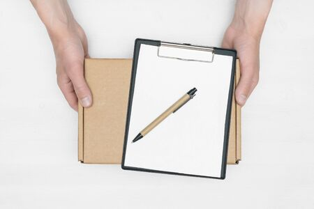 A parcel cardboard box in a delivery boy hands and a blank invoice document mock up on a white wooden table background. Delivery service concept.