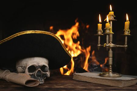 Pirate table with human skull, captain hat, book and scroll map on a burning fire background. Piracy concept.