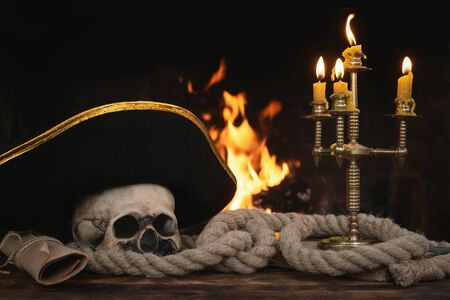 Pirate table with human skull, moorings, captain hat, book and scroll map on a burning fire background. Piracy concept.