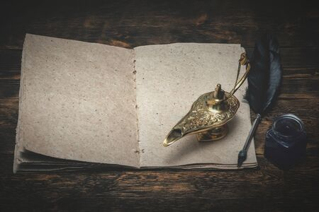 A Wish list mock up, quill pen and a golden magic lamp on a wooden board background. Fulfillment of desires concept.
