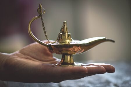 Magic lamp on the woman palm. Make a wish concept.