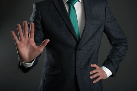 Business man is showing a stop gesture by his hand on a gray background. Shut up gesture. Stop talking concept.