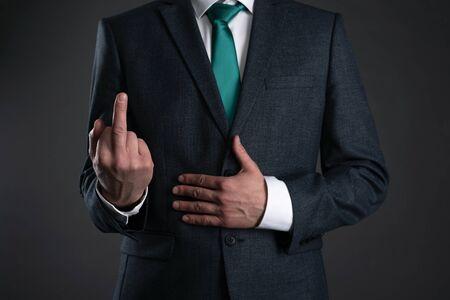 Businessman is showing a middle finger on a gray background. Impolite man. Obscene gesture. Foto de archivo