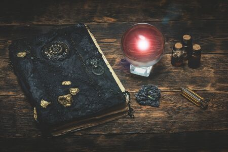 Crystal ball and a magic book on a wizard table background.