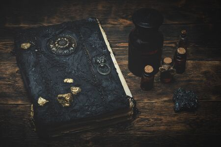 Spell book, magic potions and other witchcraft accessories on the wizard table background. Standard-Bild