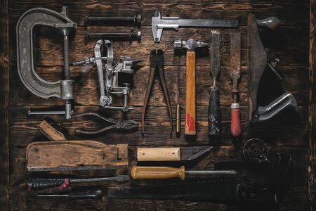 Old construction tools on a wooden workbench flat lay background. Carpenter table. Woodwork. Foto de archivo