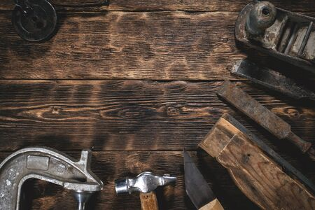 Old construction tools on a wooden workbench flat lay background with copy space. Carpenter table. Woodwork. Banque d'images
