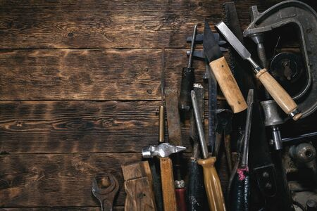 Various old construction tools on a wooden workbench flat lay background with copy space. Carpenter table. Woodwork.