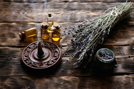 Dried lavender flower branches and lavender essential oil bottles on a wooden table background. Herbal medicine or aromatherapy concept.