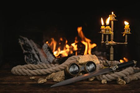 Pirate concept. Treasure hunt. Adventurer table with treasure gold, sword, binoculars and rope on a burning fire background.