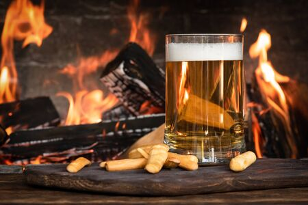 Beer in a mug and cheese sticks on a wooden table on a burning fire in a fireplace background.