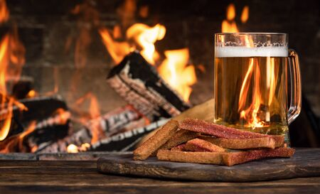 Beer in a mug and a hard chucks on a wooden table on a burning fire in a fireplace background.