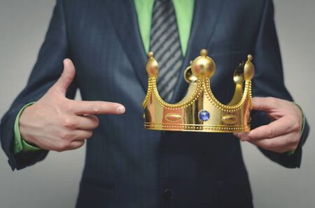 Businessman is showing on a crown in his hand. Award ceremony of the Winner. Time to rule concept. Power of authority. Crown for new king.