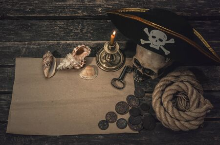Pirate treasure map with copy space, pirate captain hat, coins, human skull, seashells, mooring rope and burning candle. Treasure hunter concept background.