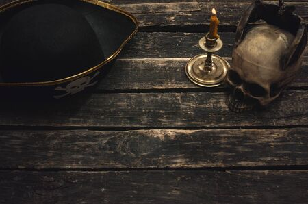 Pirate captain table with pirate hat, human skull and burning candle. Treasure hunter concept background. Reklamní fotografie