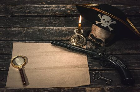 Pirate treasure map with copy space, pirate captain hat, human skull, musket, dagger and burning candle. Treasure hunter concept background.