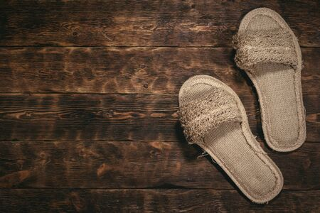 Bath slippers on a wooden floor background with copy space.