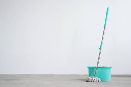 Bucket with a mop on a floor on a white wall background with copy space. Wet cleaning concept background. Foto de archivo