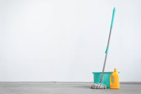 Bucket with a mop and bottle of detergent on a floor on a white wall background with copy space. Wet cleaning concept background.