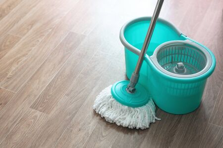 Home wet cleaning concept background. Bucket with a mop on a floor.