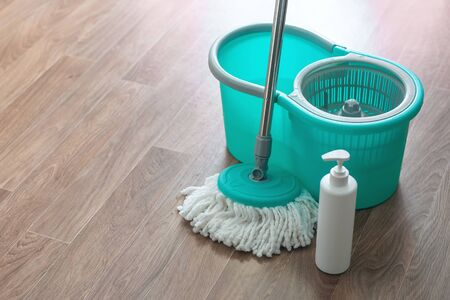 Home wet cleaning concept background. Bucket with a mop and detergent bottle on a floor.