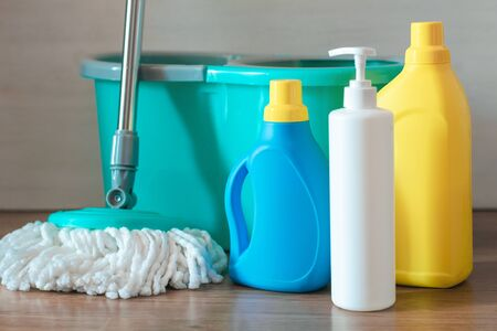 Home wet cleaning concept background. Bucket with a mop and bottles with detergent on a floor.