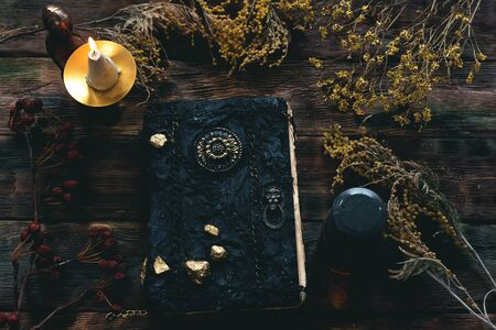 Magic recipe book of witch doctor, dried herbs and a magic potion on a wooden table. Witchcraft background. Druidism.