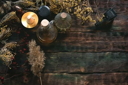 Witchcraft background with copy space. Magic potions and dried herbs on a witch doctor table.