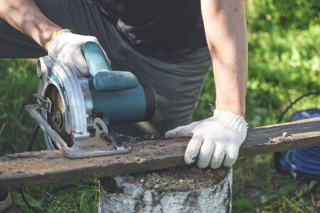 Man is cutting a wooden bar by a circular. Woodwork.