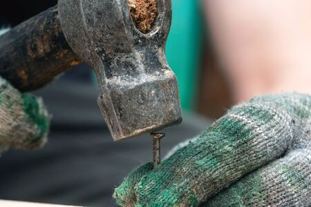 Worker is nailing a nail in a wooden board.