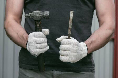 Carpenter is holding in hands a chisel and hammer.