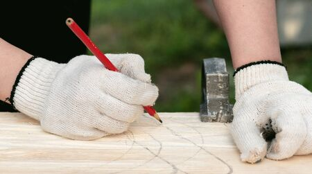 Carpenter is drawing a sketch on a wooden board by a pencil.