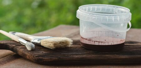 Paint brush and a jar with a brown paint on a wooden board.