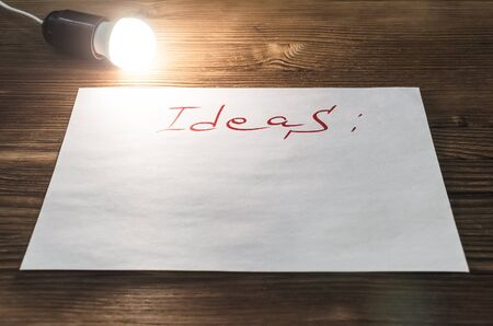 Ideas list paper page on wooden desk table surface background with copy space and burning bulb lamp. New idea.