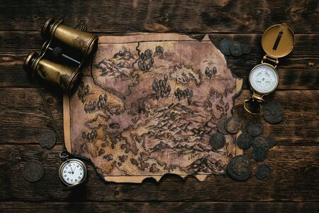 Old map, compass, binoculars and a pocket watch on a adventurer table background. Treasure hunt concept.