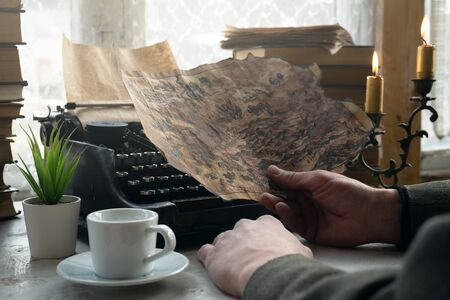 A writer is holding in hands a treasure map and is writing an adventure story on a typewriter on his desk concept.