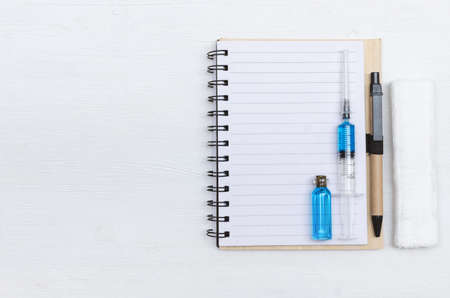 Syringe, blank page notepad, bandage and ampoule with blue liquid medicine on the doctor table. Medical journal or doctor prescription mockup.
