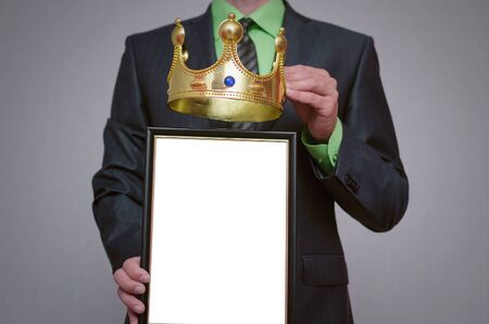 Winner blank diploma or certificate mockup in businessman hand. Man is holding a blank photo frame with copy space for human face and a golden crown above it.