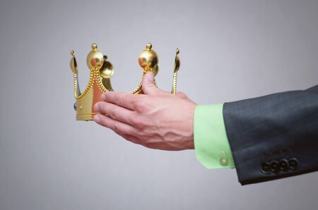 Businessman king holding in hands a gold crown and giving it to his assignee. Award ceremony concept. Winner.