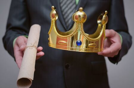 Businessman king holding in hands a gold crown and royal decree scroll (special offer document). Foto de archivo