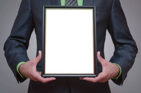 Blank diploma or certificate mock up in businessman hand. Empty photo frame border with copy space. Stock Photo