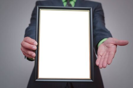 Blank diploma or certificate mock up in businessman hand. Empty photo frame border with copy space. Foto de archivo